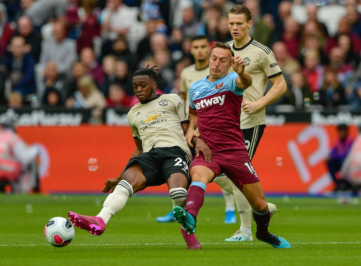 Mark Noble of West Ham United battles for the ball with Aaron Wan-Bissaka of Manchester United