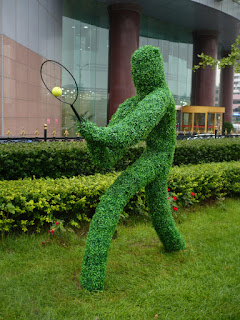 A green tennis warrior brandishes his weapon