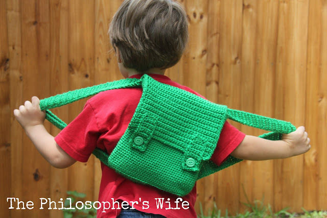 The boy is wearing a red shirt.  He is stretching his arms out, along with the green straps of his backpack.