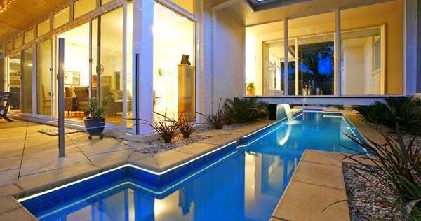 Arquitectura de casas moderna casa con piscina bajo un for Diseno de casas con piscina interior