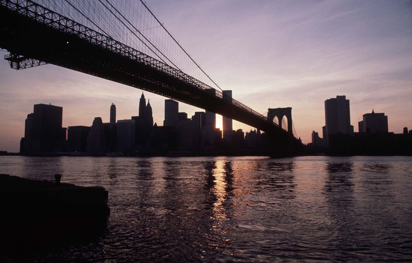 The Brooklyn Bridge and skyline of lower Manhattan remain dark as the sun sets.