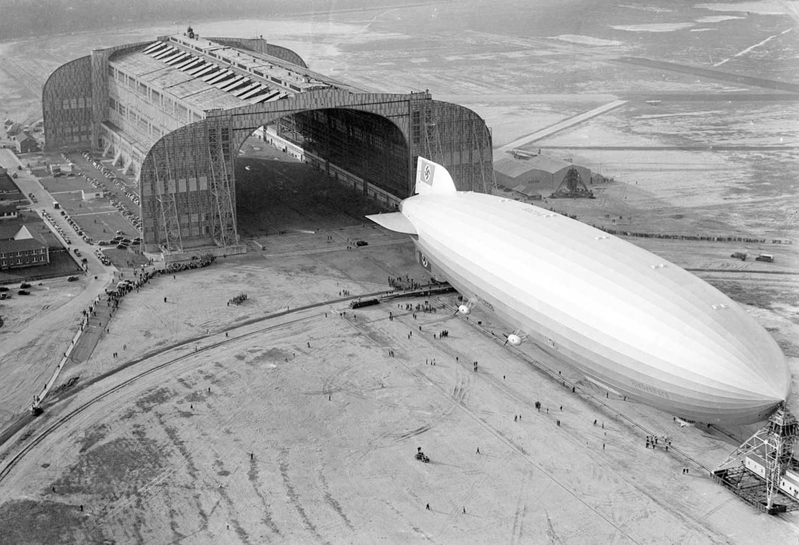 The German-built zeppelin Hindenburg trundles into the U.S. Navy hangar, its nose hooked to the mobile mooring tower, at Lakehurst, New Jersey, on May 9, 1936. The rigid airship had just set a record for its first north Atlantic crossing, the first leg of ten scheduled round trips between Germany and America.