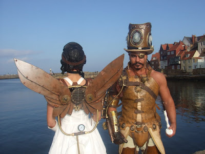 steampunk couple with wings top hat eyepatch goggles, mechanical arms