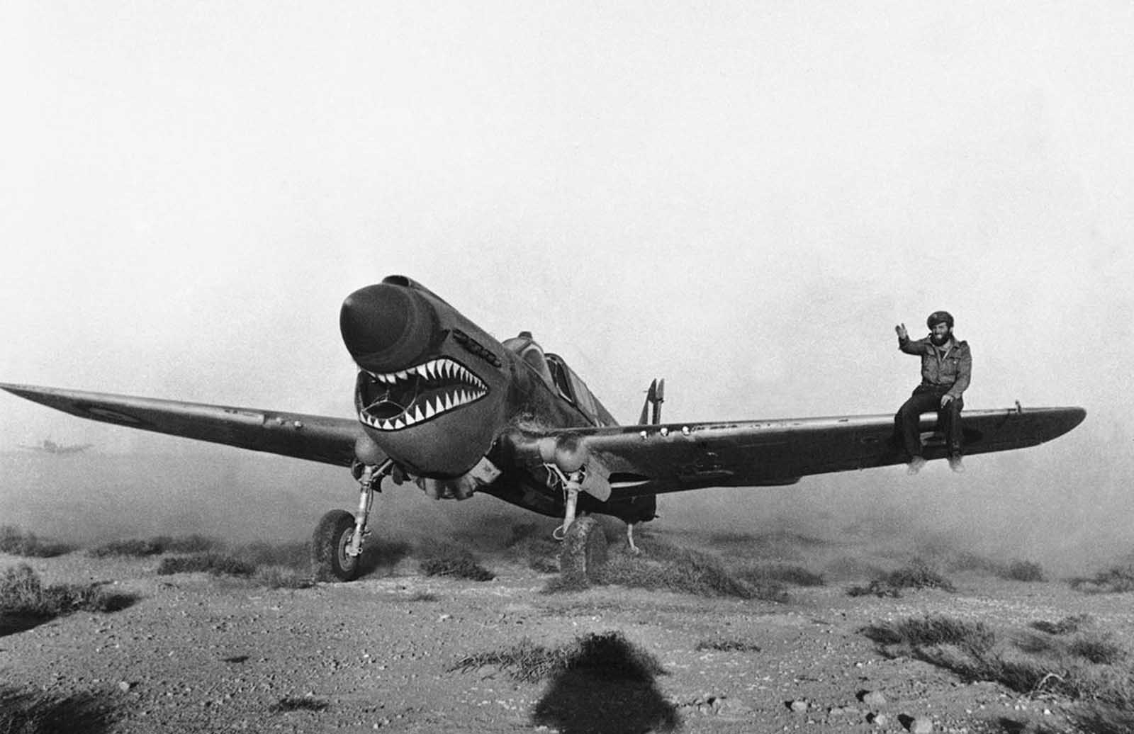 Experienced in desert weather flying, a British pilot lands an American made Kittyhawk fighter plane of the Sharknose Squadron in a Libyan Sandstorm, on April 2, 1942. A mechanic on the wing helps to guide the pilot as he taxis through the storm.