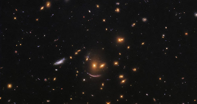 This image, taken with the NASA/ESA Hubble Space Telescope's Wide Field Camera 3 (WFC3), shows a patch of space filled with galaxies of all shapes, colors and sizes, many of which belong to the galaxy cluster SDSS J0952+3434.  Just below center is a formation of galaxies akin to a smiling face. Two yellow-hued blobs hang atop a sweeping arc of light. The lower, arc-shaped galaxy has the characteristic shape of a galaxy that has been gravitationally lensed — its light has passed near a massive object en route to us, causing it to become distorted and stretched out of shape.  Hubble captured this image in an effort to understand how new stars spring to life throughout the cosmos. WFC3 is able to view distant galaxies at an unprecedented resolution — high enough to locate and study regions of star formation within them.  Stars are born within giant clouds of gas. These massive clouds, or stellar nurseries, grow unstable and begin to collapse under gravity, becoming the seeds that will grow into new stars. By analyzing the luminosity, size and formation rate of different stellar nurseries, scientists hope to learn more about the processes that can lead to the formation of a newborn star. Studying nurseries within different galaxies will provide information about star formation at different points in time and space throughout the universe. Credit: ESA/Hubble & NASA; Acknowledgment: Judy Schmidt (geckzilla)