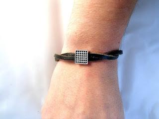 Vue sur un poignet d'un bracelet cuir noir tressé décoré d'un motif à point