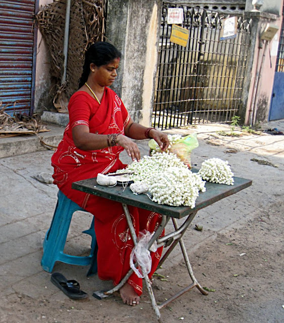 woman on street selling flower strings to decorate hair