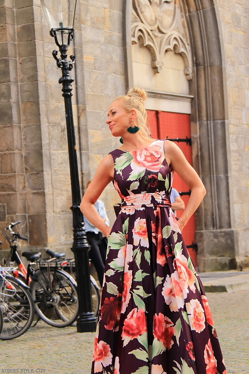 Beautiful blond dutch woman wearing her formal floral party dress in the street. Streetstyle fashion.