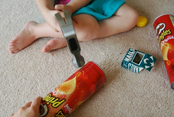 hammering nails into pringles can for rainstick