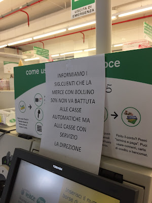 Sign asking customers to not use the automatic check-out for items discounted 50%.