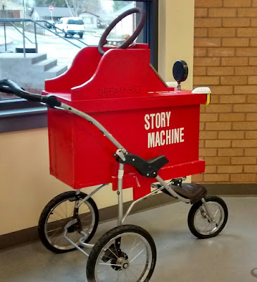 Side-view of red cart on three wheels, with handle-bars and decorative steering wheel, emblazoned with the words 'Story Machine' in white. Above, smaller black letters say, 'Dream Big.'