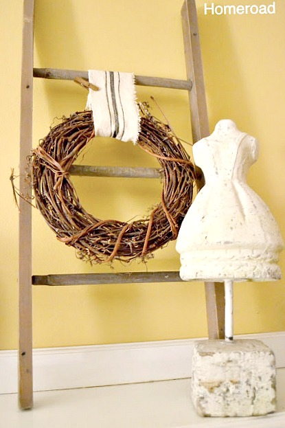ladder with a wreath and mannequin