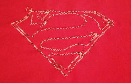 Opposite side of fabric after sewing on superhero logo applique
