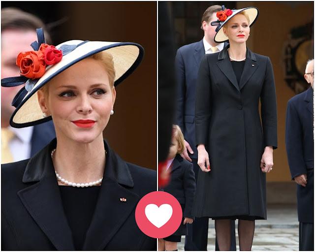 Look de Charlene con abrigo negro y tocado tipo sombrero pamela mini en color natural, lazo negro y floresen rojo y teja, labios rojos