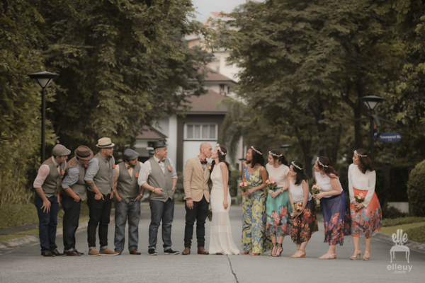 vintage and bohemian inspired wedding entourage with groomsmen wearing jeans and bridesmaids wearing floral skirt and crown