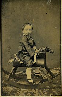 Niño con su caballito antiguo de juguete