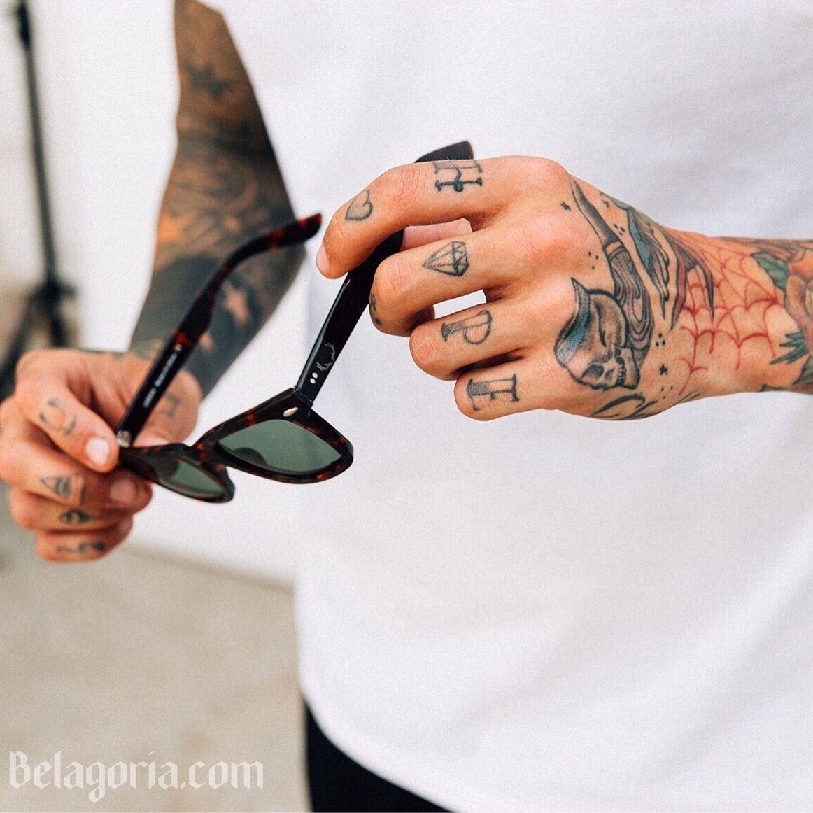 Las manos de un chico con tatuajes sencillos
