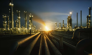 Gas fires at an oil refinery glows in Saudi Arabia. Investment projections by the International Energy Agency remain massively skewed towards oil and gas, a new report claims. (Photograph Credit: Thomas J. Abercrombie/National Geographic/Getty Images)) Click to Enlarge.