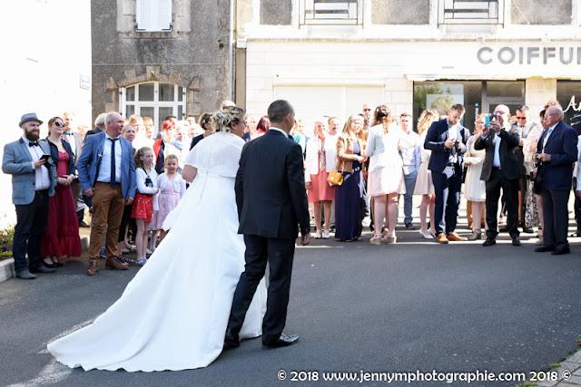 mariés vue de dos devant leurs invités devant l'église