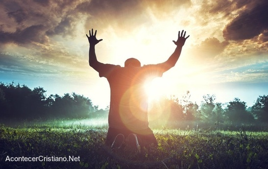 Hombre orando de rodillas con las manos levantadas