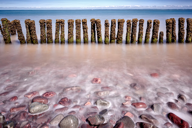 Porlock beach groynes with waves lapping over colourful stones by Martyn Ferry Photography