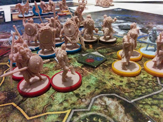 A group of beige figurines and one pale blue-grey figurine, all resembling the stereotypical image of Vikings, with red, yellow, or dark brown bases to differentiate player factions, in the central space of the game board. The board represents an island divided into various provinces, painted to look like generic Nordic terrain. A square token can be seen in each province with one of three symbols: a hand holding lightning bolts, an axe head, and a stereotypical Viking helmet complete with anachronistic horns. The tile in the center province contains all three of these symbols.