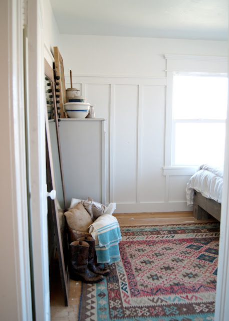 Farmhouse Master Bedroom Reveal - Benjamin Moore Simply White, Paint by number cow painting . antique crocks, red wing, chicken feeder, books, mason jars, fusion mineral paint putty, kilim rug