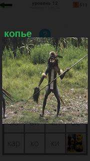 на поляне стоит индеец в раскраске и держит копье в руках