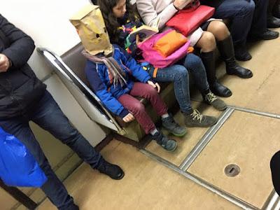Papiertüte über Kopf - lustiges Kind in Straßenbahn