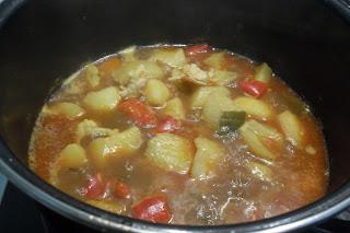 Incorporando el caldo de pescado para las patatas con gambas y pimiento