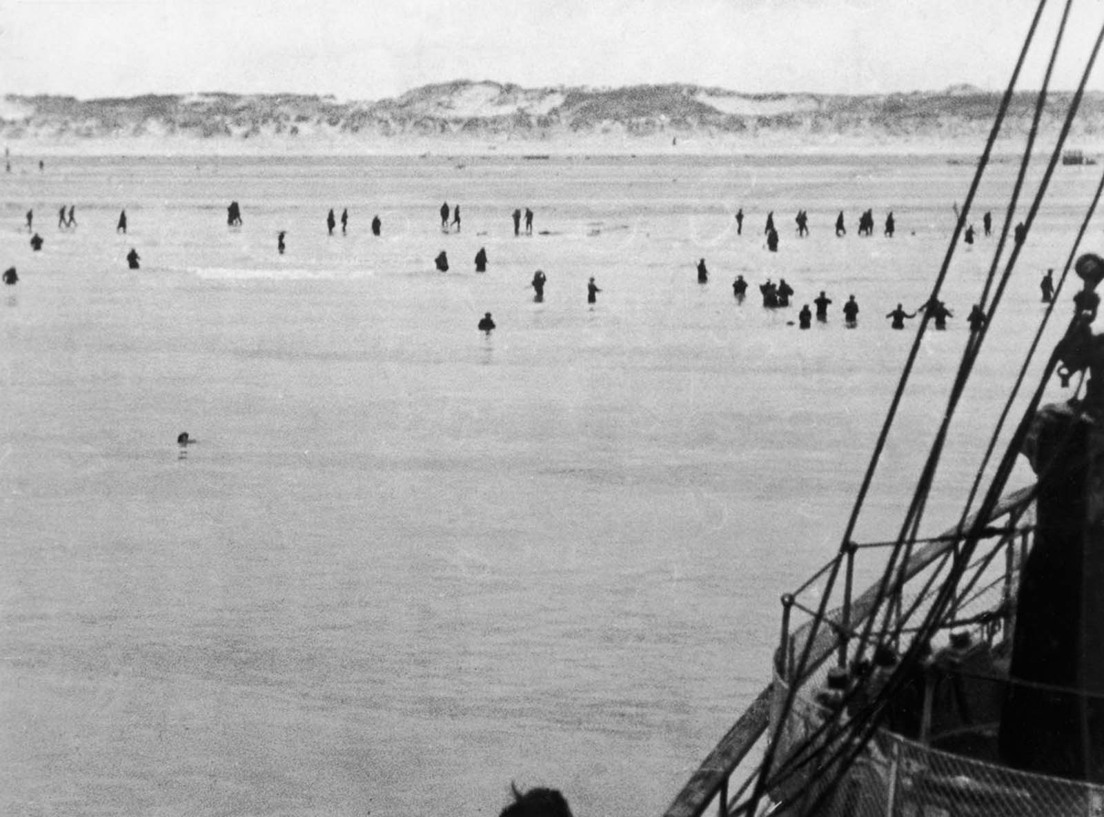 British and French troops wade out to evacuation ships off Dunkirk beach.