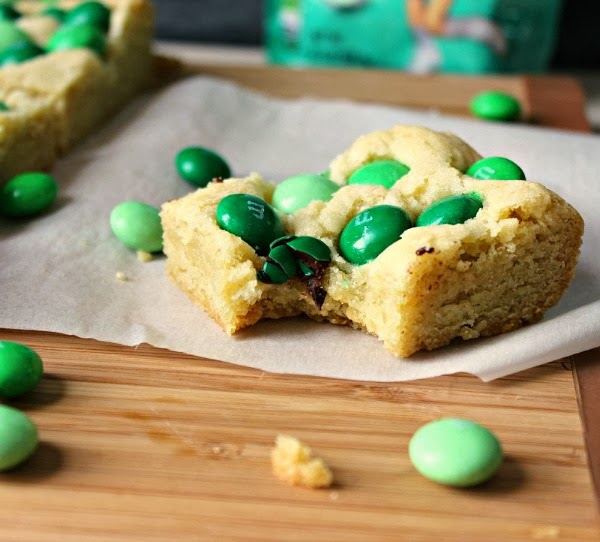 Mint M&M Sugar Cookie Bar dotted with green m&m's with a bite taken out!