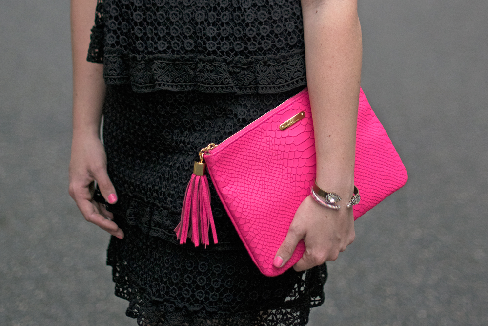 Black guest dress with pink clutch.