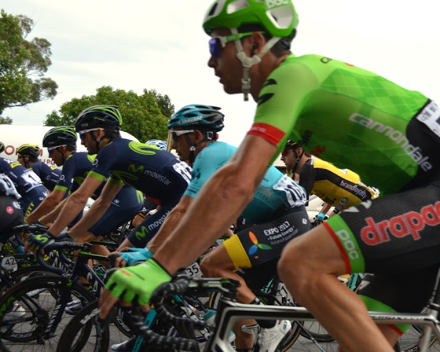 A side-view of the pack with the riders on their bikes facing the left-hand edge of the picture. The bright green in front is Cannondale-Drapac, with Astana behind it in light blue. Slightly ahead in the row are the dark colours of Movistar with green bands around the sleeve cuffs) and Orica.  The yellow streak with a black stripe (underneath the green Cannondale-Drapac) is Lotto-Jumbo.