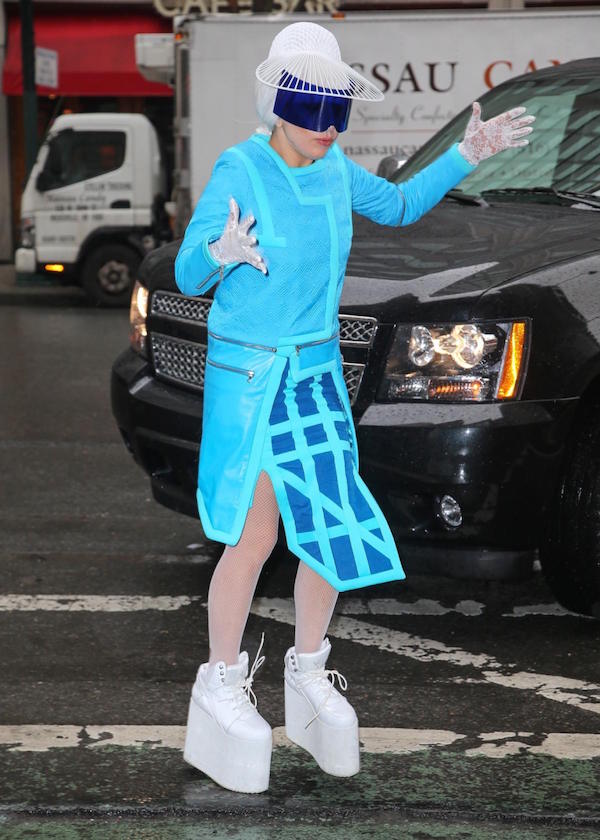 A Bright blue neon outfit with high platform sneakers and kinda look like robotic glasses.
