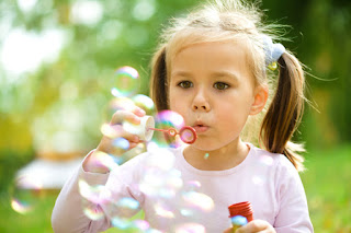 Photo of a Little Girl Blowing Bubbles