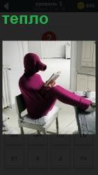 человек на стуле для тепла оделся с ног до головы в фиолетовый костюм