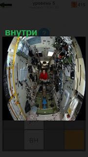 Внутри помещения с приборами и освещением сидит мужчина в красной рубашке