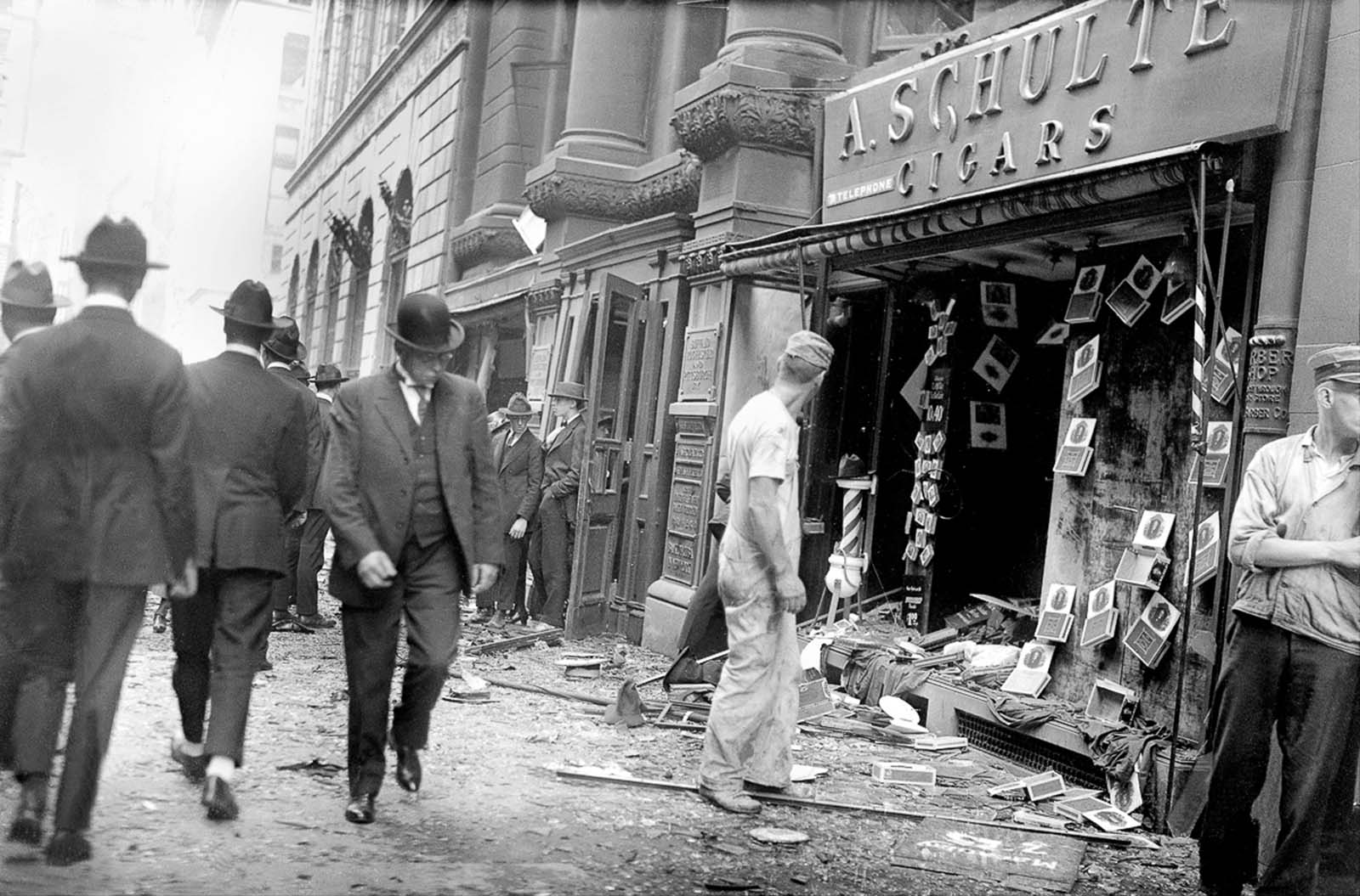 Bystanders walk by the wrecked facade of a cigar store.