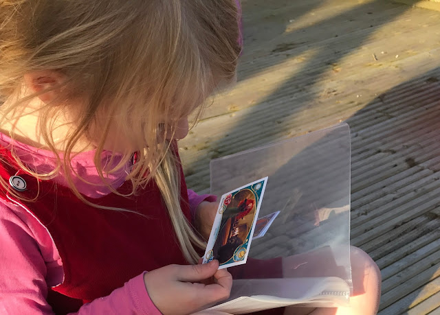 A young blonde girl sitting on decking looking at a Topps Disney Princess Trading card from Brave while holding a clear binder