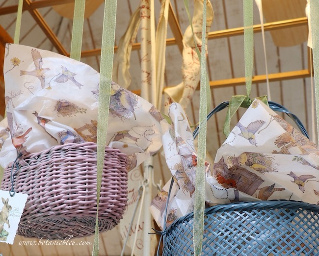 Spring baskets in pastel colors have bird tissue paper in the garden shed