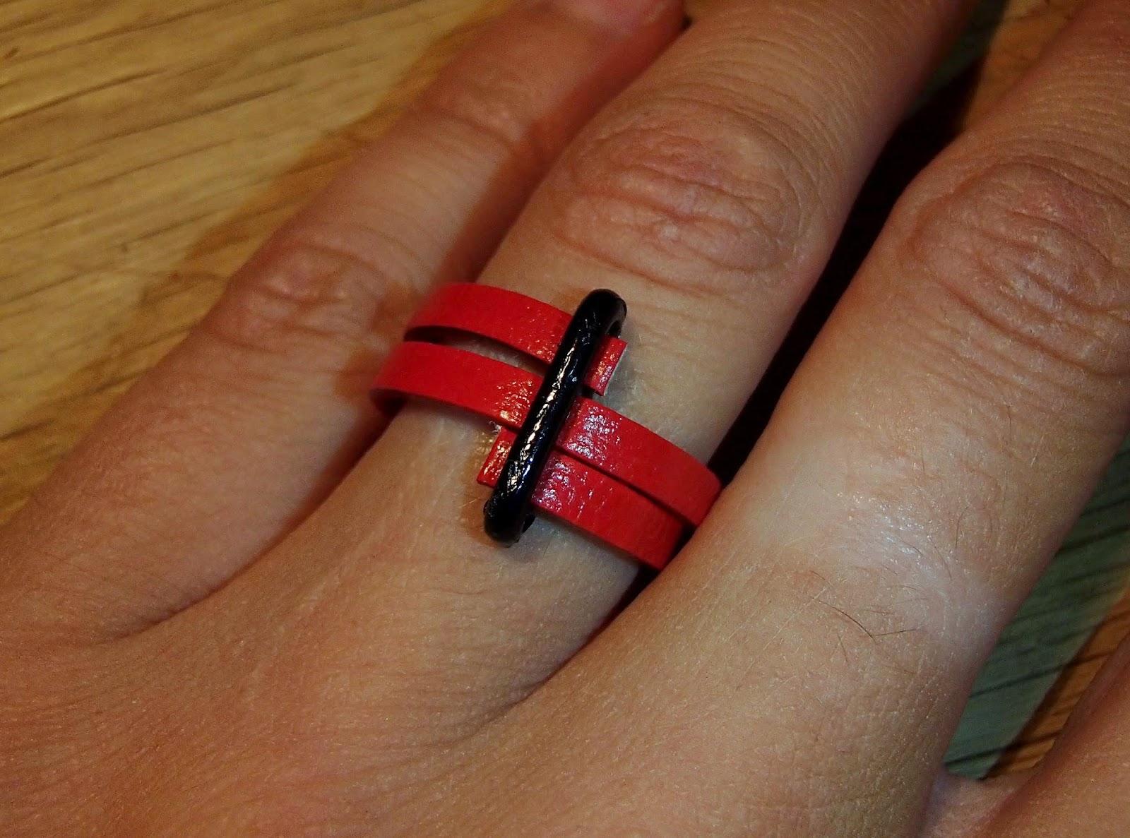 Vue sur une main de la bague verticale rouge en cuir plat