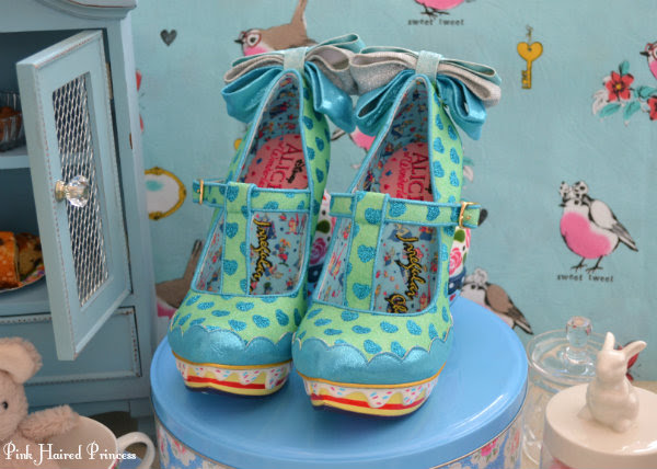front view of Irregular Choice Alice My Cup Of Tea shoes with cakes and tea party themed background