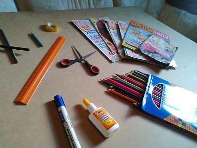 Revistas viejas listas para reciclar sobre una mesa de trabajo, con tijeras, cinta, pegamento, regla, marcador, lápices y caja de colores