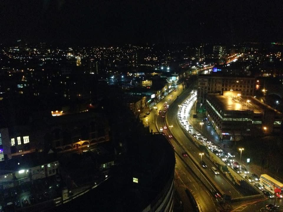 the view from the hotel window at night. the streets can be seen lit up with street lights and car lights