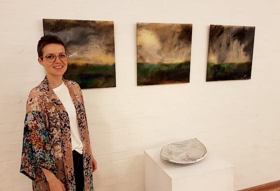 Louise Egedal med tre af sine malerier og et keramikfad