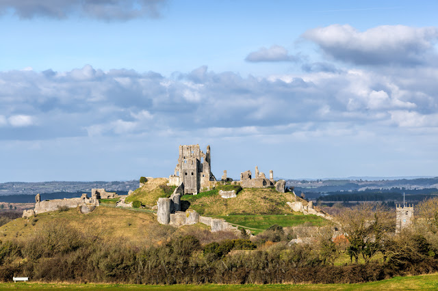 Ruins of Corfe Castle atop a hill surrounded by the Dorset landscape