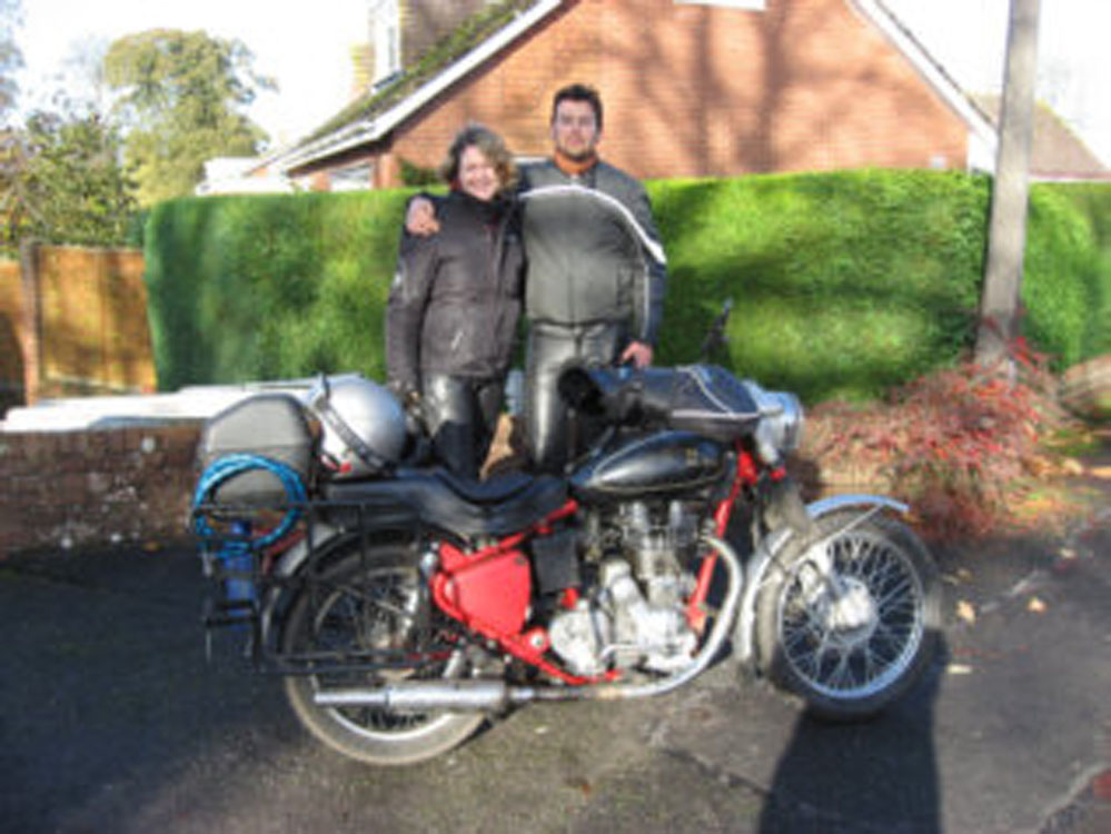 Couple poses with their motorcycle.