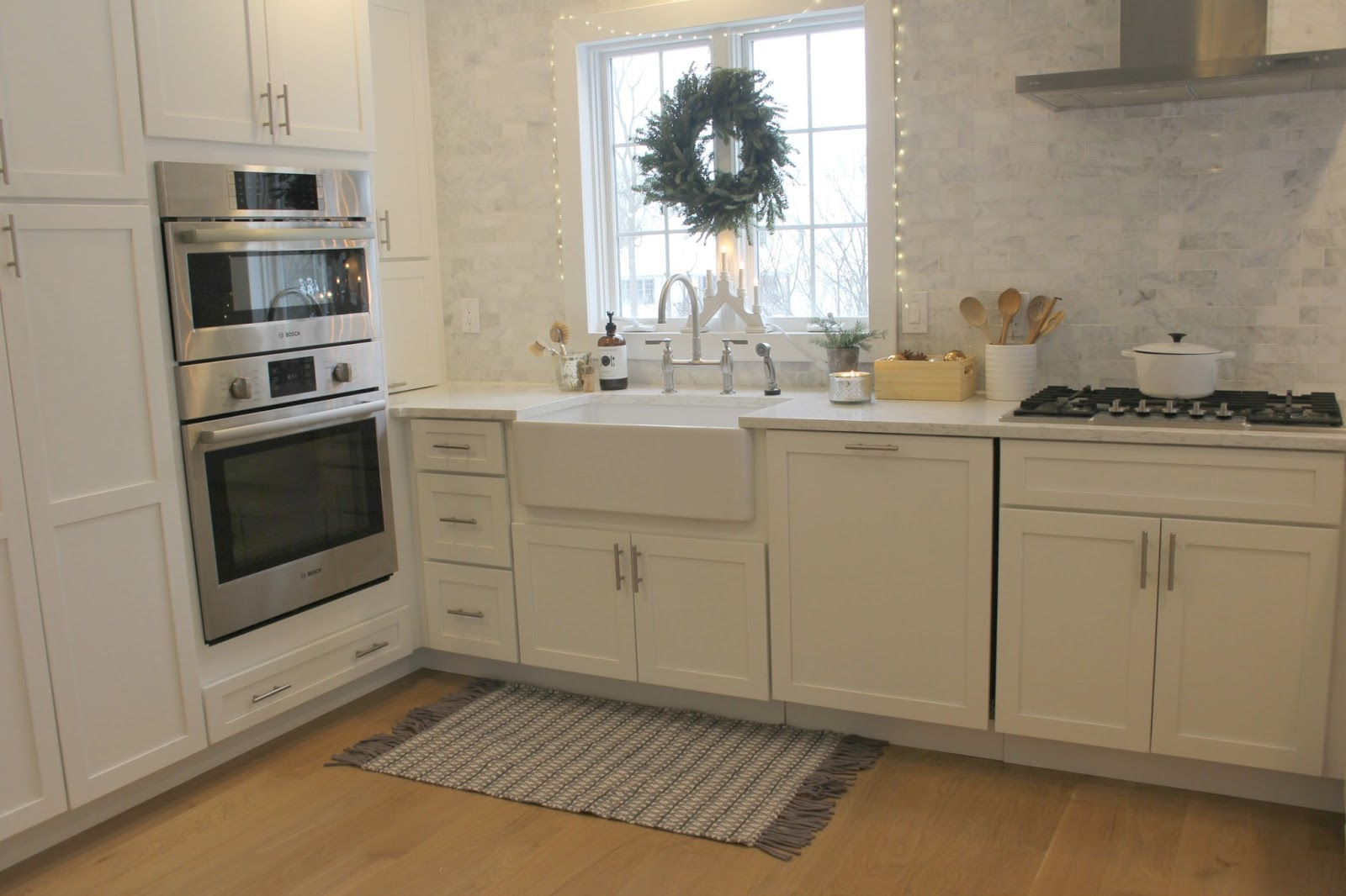 White Shaker style kitchen with farm sink and fresh green wreath