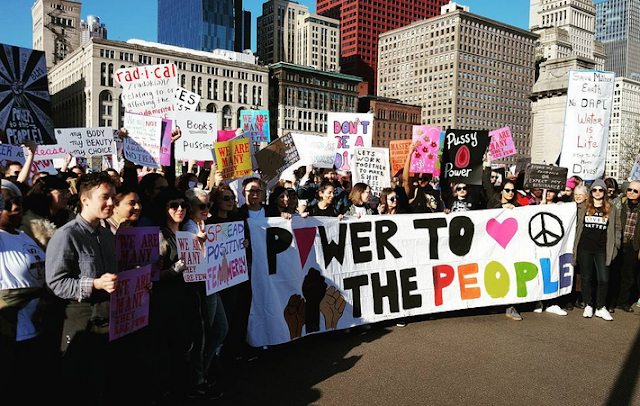 """Crowd in front of Chicago skyline. People holding signs and banner reading """"Power to the People"""""""